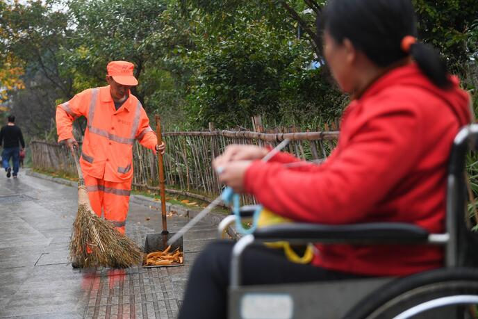 ↑1月9日,董锦香坐着轮椅一边织毛衣,一边陪丈夫董基东清扫路面。