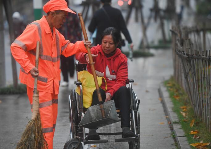 ↑1月9日,董锦香帮董基东运送用来清扫路面的工具。