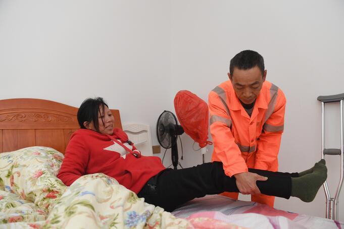 ↑1月9日,董基东在家中扶董锦香上床休息。