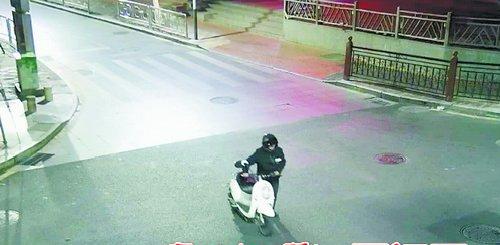 身穿黑色服装、戴着头盔的嫌疑人推走一辆白色电动车,被监控设备记录下来。