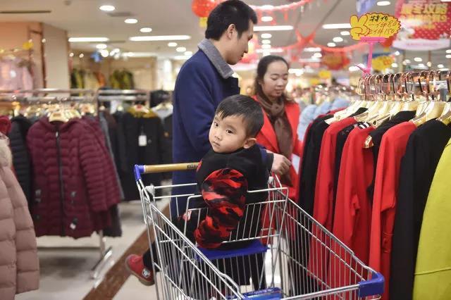 黄海龙、黄爱华带着小聪聪在超市选购过年回家送家人的衣服。