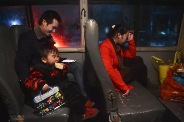 在超市的免费班车上,逛了一下午的小聪聪有点儿疲惫,饿得啃起了一块沙琪玛。小聪聪的手里拿着爸爸妈妈给他买的新年礼物——玩具车。