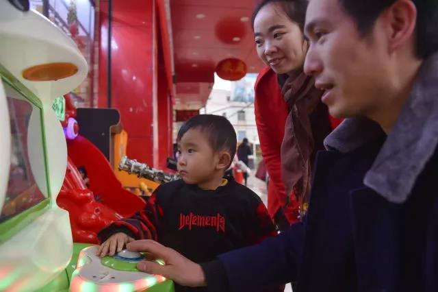 黄海龙、黄爱华带着小聪聪在街头玩游戏机。服装厂开工的时候,他们很少有时间陪小聪聪上街玩。