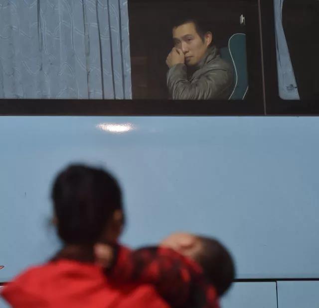 长途车上的黄海龙看着哭闹的儿子,用手擦着眼泪。