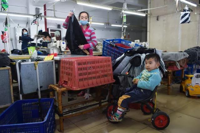 黄爱华在工作之余照看在旁边骑玩具车的聪聪。