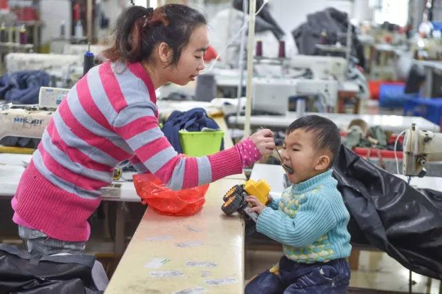 黄爱华在工厂给聪聪喂午饭。