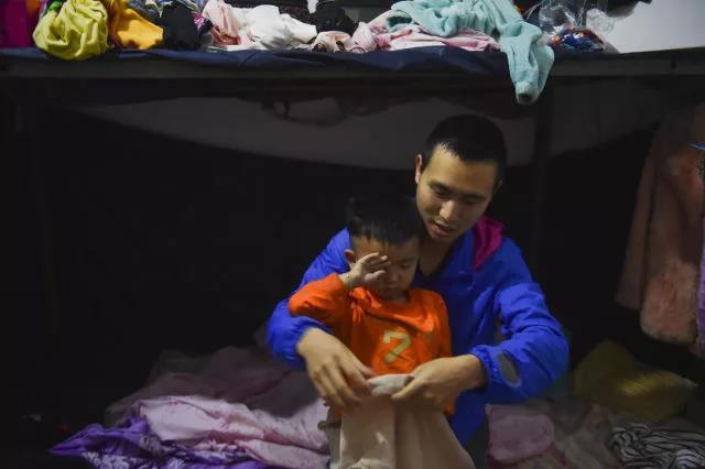 在工人宿舍,睡眼惺忪的聪聪在父亲黄海龙的帮助下穿衣服,准备去幼儿园。