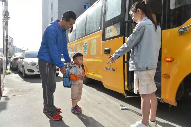 在厂门口,黄海龙(左)将聪聪送上去往幼儿园的校车。