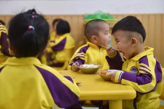 在福建省石狮市鹏博幼儿园,刚刚入园一个月的聪聪(右一)在吃饭。