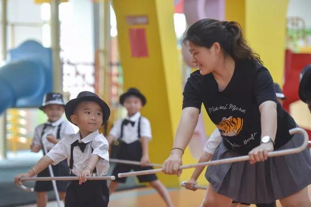 """在福建省石狮市鹏博幼儿园,聪聪(左)跟着老师林慧芬排练""""六一""""节目。"""