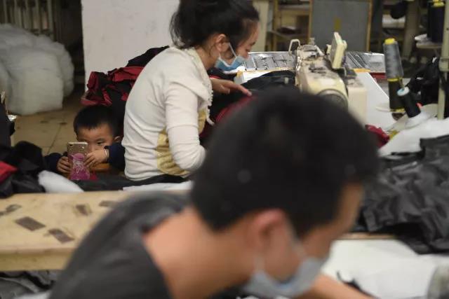 聪聪坐在父母的工位旁看手机。