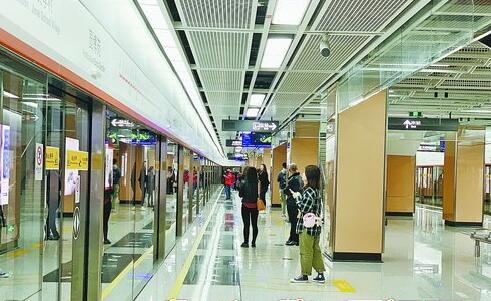 乘客们自觉站在安全黄线后等候地铁列车到来。