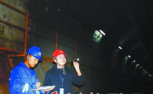 沈峰(右)在施工现场查看工程进展。