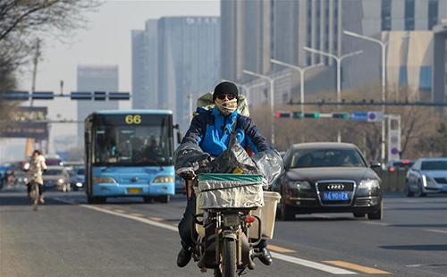 2019年1月23日,程泓毅骑着电动车在呼和浩特市的街道上运送快递。