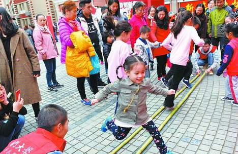 小朋友在游园活动中跳竹竿舞