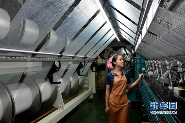 2018年12月21日,民营企业福建华峰新材料有限公司工人在生产制鞋面料。(新华社记者张国俊 摄)