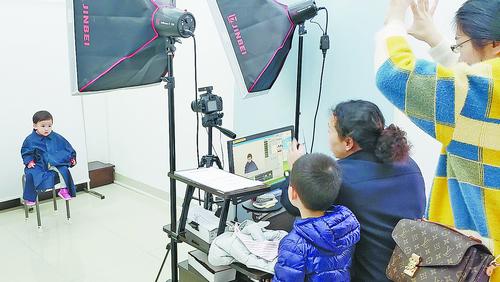 嘉莲派出所户籍民警耐心地协助家长帮孩子拍照。