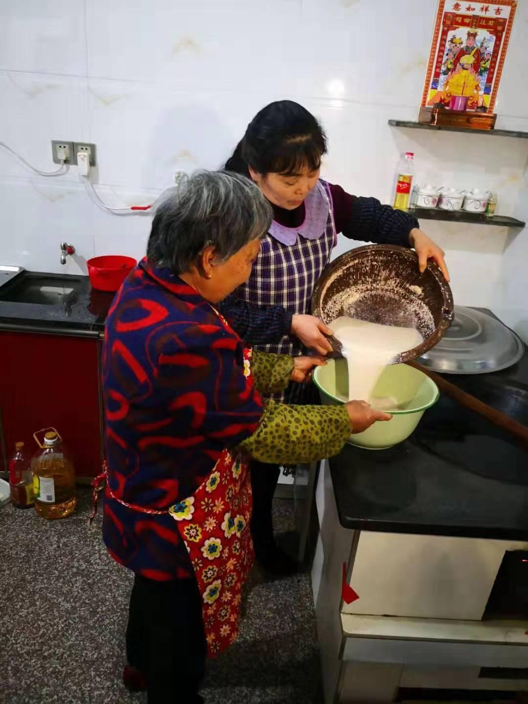 这是邱彩立(右)和邻居一起做擂茶