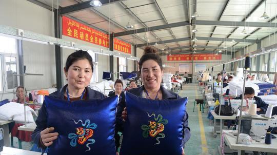 3月29日,工人们展示刺绣成品。