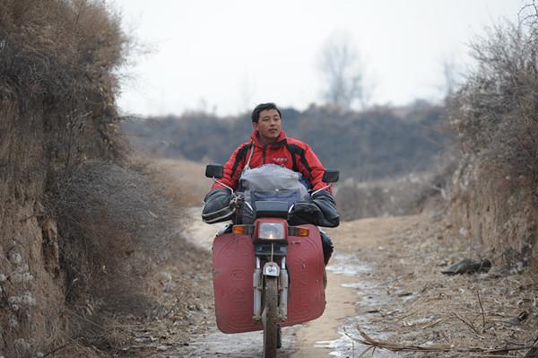贺星龙骑着摩托车出诊