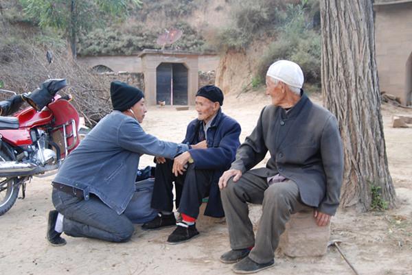 贺星龙在村头给村民看病