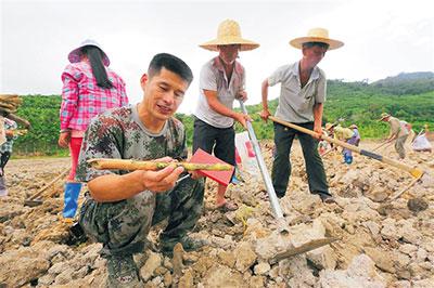 隋耀达在地里与村民研究如何种好牧草