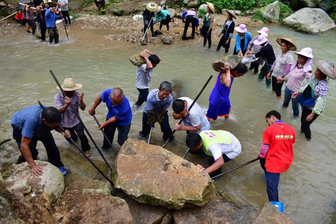 ↑在黔桂交界的乌英苗寨,驻村第一书记韦桂华(前右二)和群众一起修河堤(7月3日摄)。