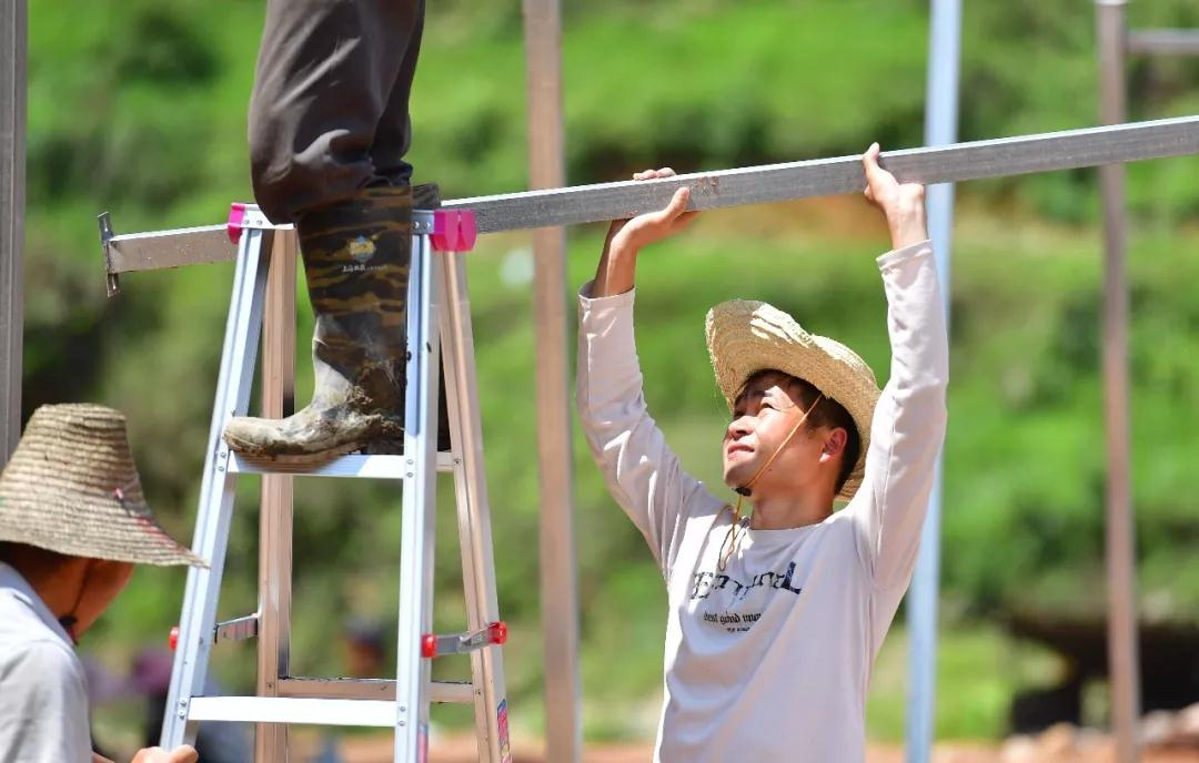 ↑在融水苗族自治县杆洞乡党鸠村木耳种植基地,扶贫工作队队员黄鼎业和群众在搭建大棚(6月2日摄)。