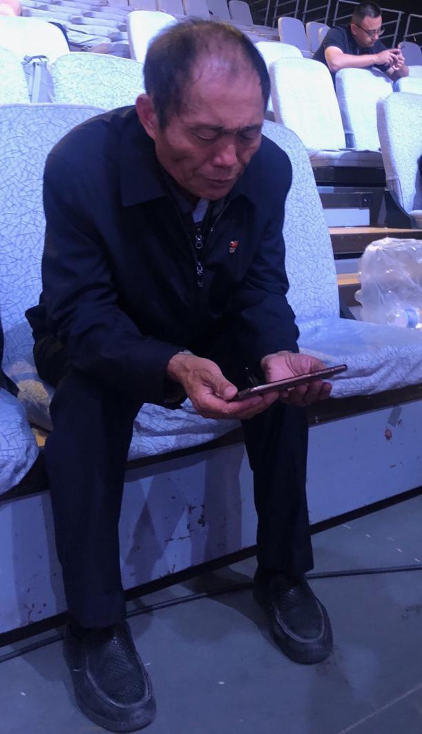 图为李连成拿着手机正在重温自己的入党志愿