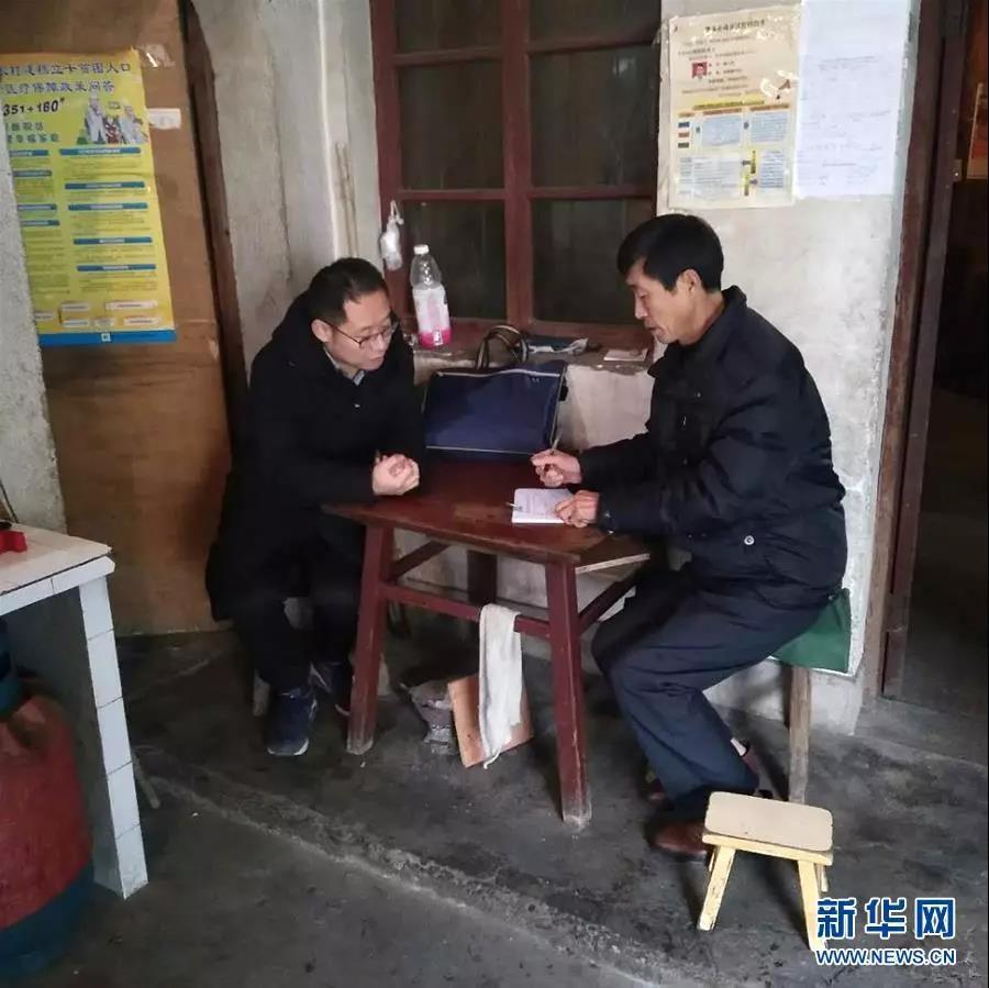 李夏(左)在贫困户家中走访(资料照片)。  新华社发
