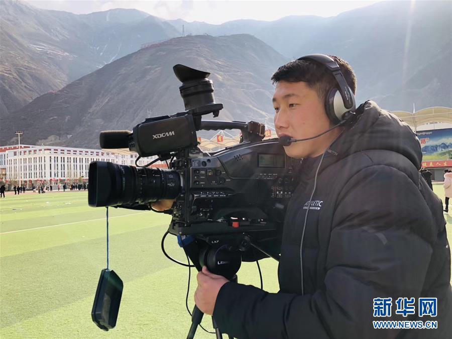 闵江伟在2019年舟曲县春节民俗文化活动现场参加现场直播(2019年2月14日摄)。新华社发