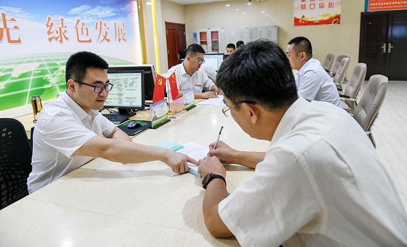 2019年7月16日,在内蒙古自治区自然资源厅的自然资源政务大厅内,办事员(左)为采矿企业办理相关审批手续。新华社记者 彭源 摄