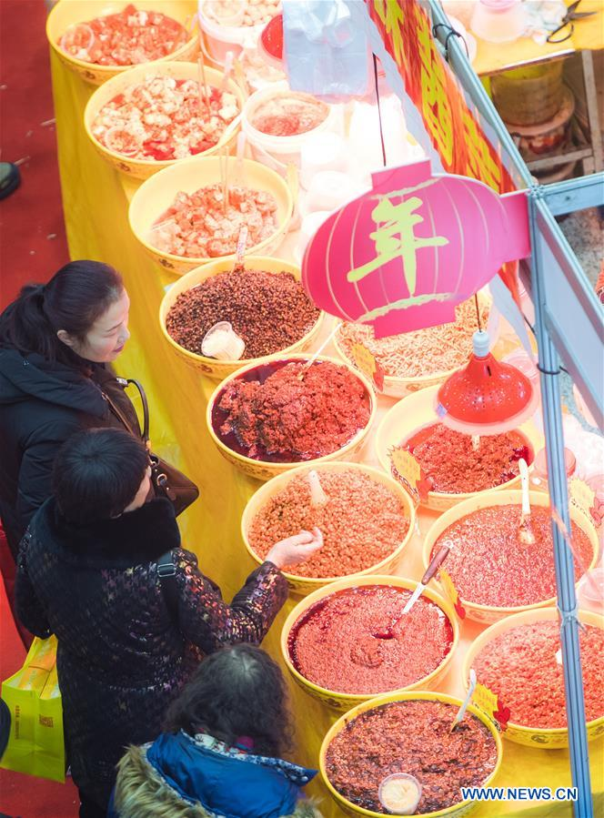 Residents select goods at a shopping fair held to greet the upcoming Spring Festival at Wuhan International Conference & Exhibition Center in Wuhan, capital of central China