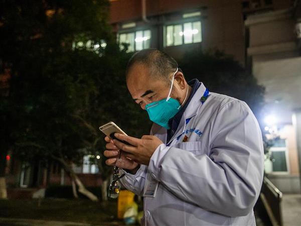 1月27日晚,武汉市金银潭医院,张定宇在等待危重病人转运时接到病人心跳停止的紧急电话,抓紧联系协调处理。
