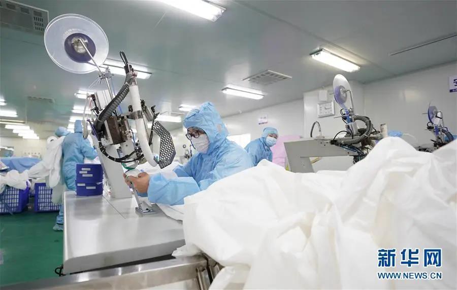 在位于武汉市新洲区的武汉协卓卫生用品有限公司,工人们在赶制防护服(1月28日摄)。新华社记者 才扬 摄