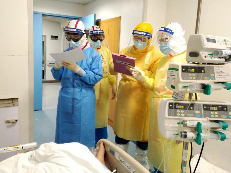 2月11日,在武漢同濟醫院中法新城院區ICU病房內,來自北京協和醫院的醫護人員在病床旁查房交班。