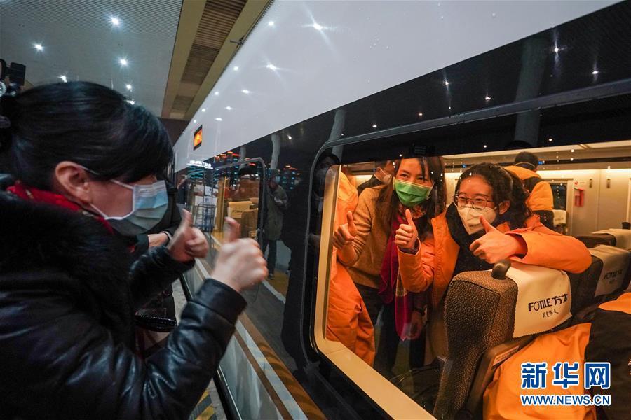 1月25日,送站亲友在铁路南京南站站台为医疗队队员打气加油。当日,首批江苏援湖北医疗队从南京集结出发,奔赴武汉。 新华社记者 李博 摄