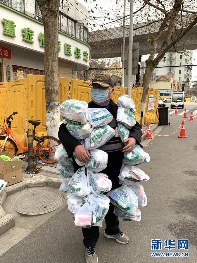 2月24日,在武汉市江岸区黄石路汉口大药房,惠民苑社区网格员丰枫把为居民购买的药挂在身上。 新华社发