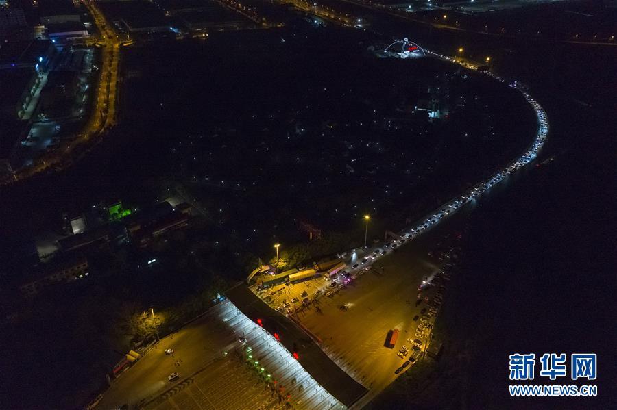 """4月8日凌晨,武汉""""解封""""后,车辆通过武汉西高速收费站(无人机照片)。 新华社记者 沈伯韩 摄"""