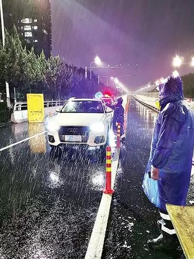 凌晨,东瓯大桥卡点处,永嘉县党员干部顶风冒雨、在严寒中牢牢值守。( 图片由浙江省温州市委组织部提供)