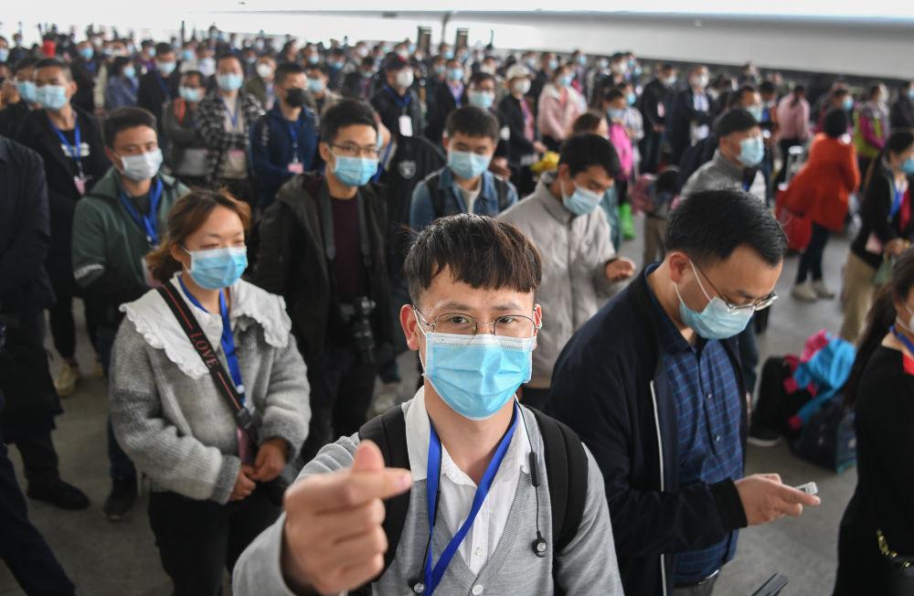 3月19日,在湖北荆州火车站,务工人员陈安心(前)准备上车。当日,551名荆州务工人员搭乘G4368专列抵达广州,返岗就业。新华社记者 程敏 摄