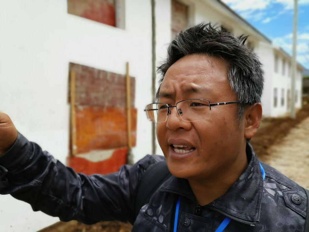 四川省布拖县乐安乡党委副书记木乃什古在查看建设中的洛恩村安全住房路面质量(5月23日摄)。新华社记者 谢佼 摄