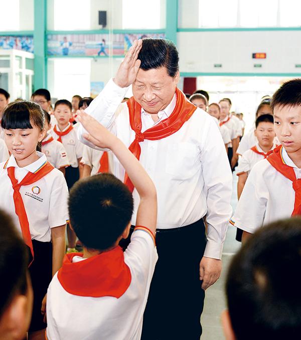 """2014年5月30日上午,中共中央总书记、国家主席、中央军委主席习近平来到北京市海淀区民族小学,参加庆祝""""六一""""国际儿童节活动。这是习近平参加少先队入队仪式。 新华社记者 李涛/摄"""