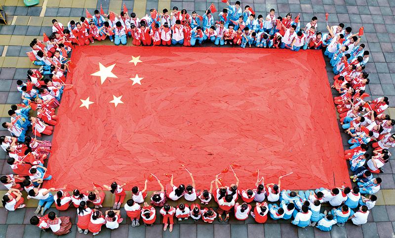 """社會主義辦學方向是我國教育最鮮亮的底色,我國教育要培養的是社會主義建設者和接班人,這是個根本性的問題。圖為山東省沂源縣荊山路小學開展""""紅領巾拼國旗祝福祖國迎國慶""""活動,學生們在老師帶領下用紅領巾拼出了一面巨型國旗,表達對偉大祖國的祝福。 教育部供圖"""