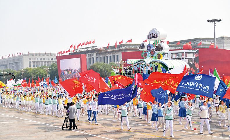 """2019年10月1日,在慶祝新中國成立70周年大會群眾游行活動中,""""立德樹人""""方陣的教師和學生代表們揮舞著鮮花和校旗,伴著歌聲走過長安街。 新華社記者 李尕/攝"""