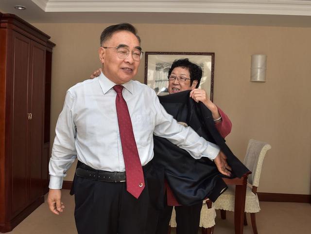 """9月8日上午,""""人民英雄""""国家荣誉称号获得者张伯礼在出发前由妻子协助穿衣。新华社记者 李贺 摄"""