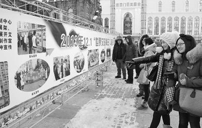 工作人员通过艾滋病防御与治疗图片展板和倡议签名等