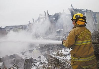 一名消防员向地震引发火灾的区域喷洒泡沫