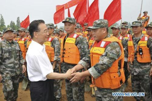 Chinese Premier Wen Jiabao (L, front) visits soldiers at a stone storing site at Huaihe River dike, east China's Anhui Province, July 24, 2010. Wen Jiabao Saturday visited Anhui Province to inspect the flood control operations along the Huaihe River. (Xinhua/Huang Jingwen)