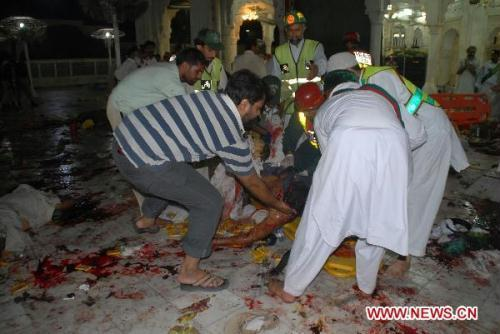 Rescuers carry a body from the blast site in eastern Pakistani city of Lahore on July 2, 2010. At least 37 people were killed and 175 others injured in three suicide bomb attacks at a shrine in Lahore late Thursday night, according to local sources and media reports. (Xinhua/Jamil Ahmad)
